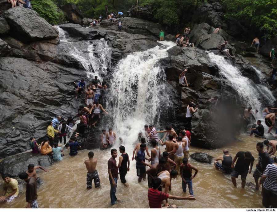 Group Enjoying Under Waterfall